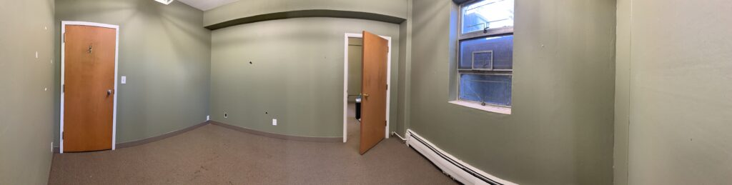 A panoramic photo of the available office space in the building, showing two rooms with green walls. Two doors and a window can also be seen.