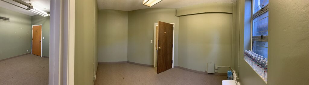 Image of available office space, showing a room with green walls that opens open into the second office space. There is one window.